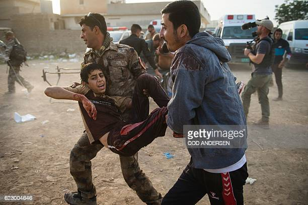 Graphic content / An Iraqi soldier and neighbour rush 12yearold Mohammed to an outdoor field clinic in the Samah neighbourhood in Mosul on November...