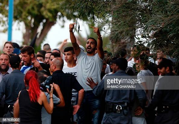 Graphic content / An Israeli protestor gestures towards Palestinians demonstrating against administrative detention and in support of Palestinian...