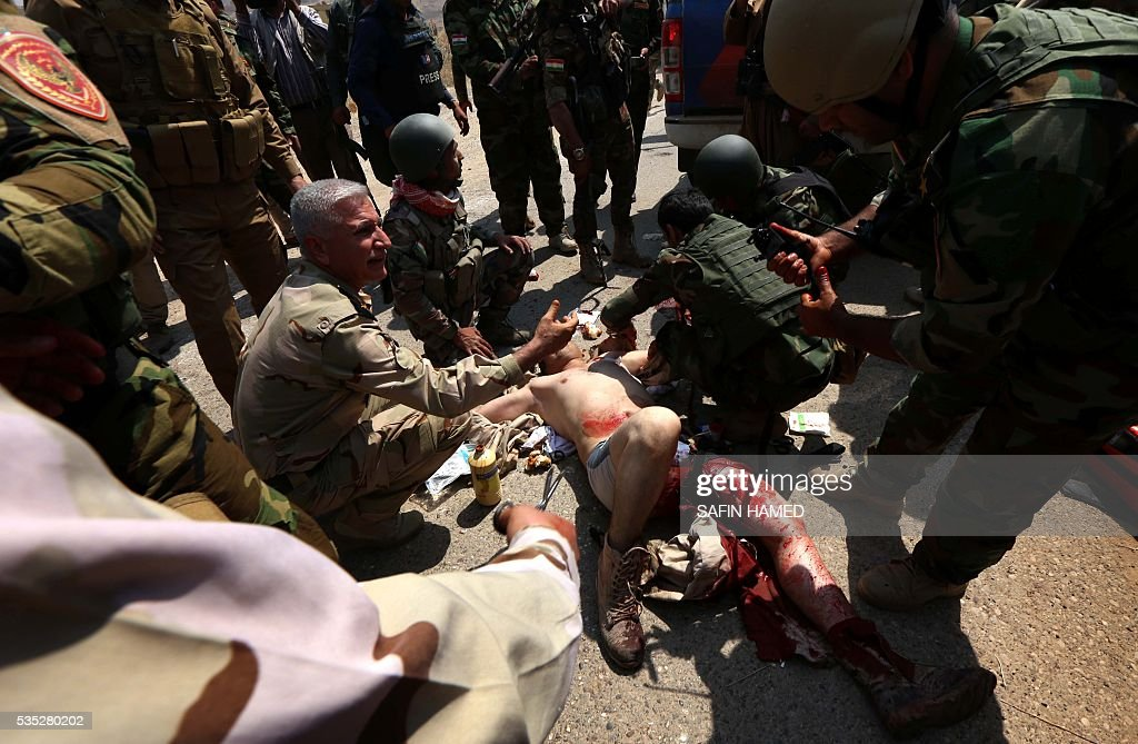 Graphic content / An wounded Iraqi Kurdish Peshmerga fighter receives treatment during a operation near Hasan Sham village, some 45 kilometres east of the city of Mosul, aimed at retaking areas from the Islamic State group on May 29, 2016. The 'peshmerga-led ground offensive, backed by international coalition warplanes' started before dawn, the Kurdistan Region Security Council (KRSC) said. The fresh push against the jihadist organisation comes a week after Iraqi forces launched an operation against Fallujah, IS's only other major urban hub in Iraq. / AFP / SAFIN