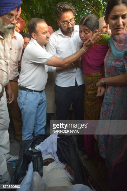 Graphic content / Baljit Kaur and her son Amritbir Singh look at the body of her husband Indian Central Reserve Police Force personnel Raghbir Singh...