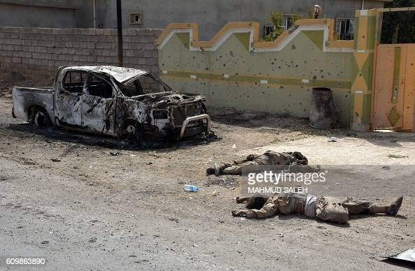 Graphic content / Bodies of fighters lie on the ground near a charred car in the Iraqi town of Sharqat 260 kilometres northwest of Baghdad and around...