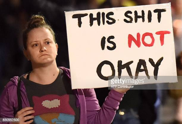 Graphic content / Charlotte Brockton holds up a sign while marching with protesters again racism in Oakland California on August 12 2017 Protesters...