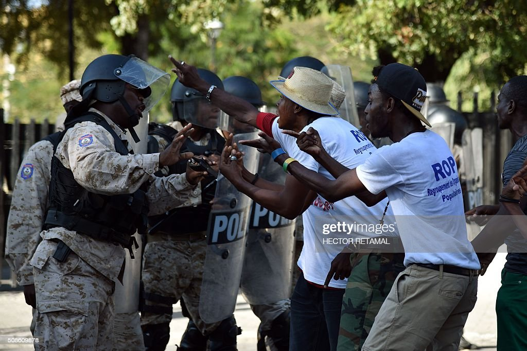 Graphic content / Demonstrators talk to haitian police in front of the National place during a protest agaist President Michel Martelly and for a transitional government in Port-au-Prince on February 5, 2016. President Michel Martelly's term ends February 7, and with no successor in place, Haiti is facing constitutional crisis. Haiti's electoral authority postponed the planned January 24 presidential run-off amid mounting opposition street protests and voting fraud allegations. / AFP / HECTOR