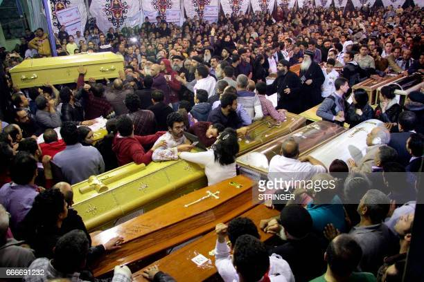 Graphic content / Egyptian Christians gather around and carry coffins during the late night funeral of the victims of a blast which killed...