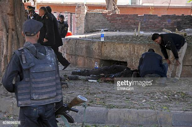 Graphic content / Egyptian security forces check a body at the site of a bomb attack next to a police checkpoint in the western Talibiya district of...