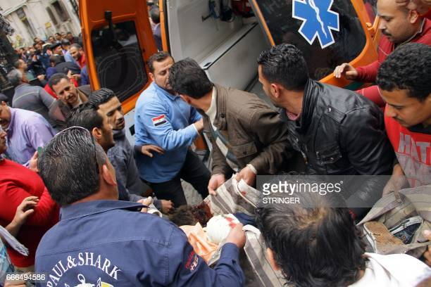 Graphic content / Egyptians load a body onto an ambulance near a church in Alexandria after a bomb blast struck worshippers gathering to celebrate...