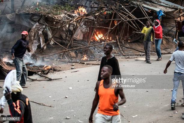Graphic content / Food stalls belonging to traders from the Kikuyu ethnic group are burning after they were set on fire by Luo tribemen during a...