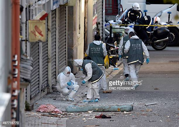 Graphic content / Forensics of the French police search for evidence next to the remains of a human head outside a building in the northern Paris...
