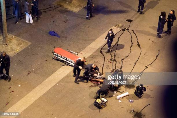 Graphic content / French fire fighters rescue a man laying of the floor after being stabbed on the leg as French police officers stand guard around...