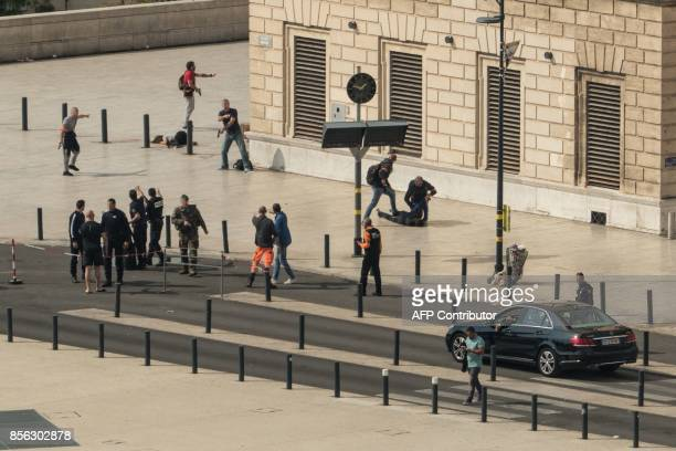 Graphic content / French police turn over and hold the body of a man on the ground while other policemen surround the body of a stabbed woman while a...