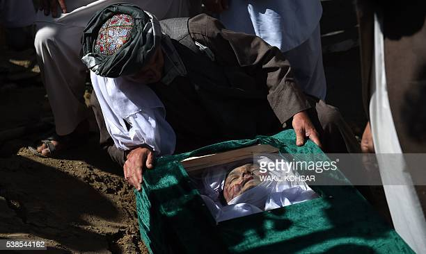 Graphic content / Friend and relatives lower the coffin of Afghan reporter Zabihullah Tamanna during his burial ceremony at the Shuhada cemetery in...