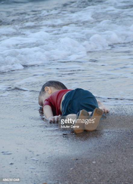 A migrant child's dead body lies on the shores in Bodrum southern Turkey on September 2 2015 after a boat carrying refugees sank while reaching the...
