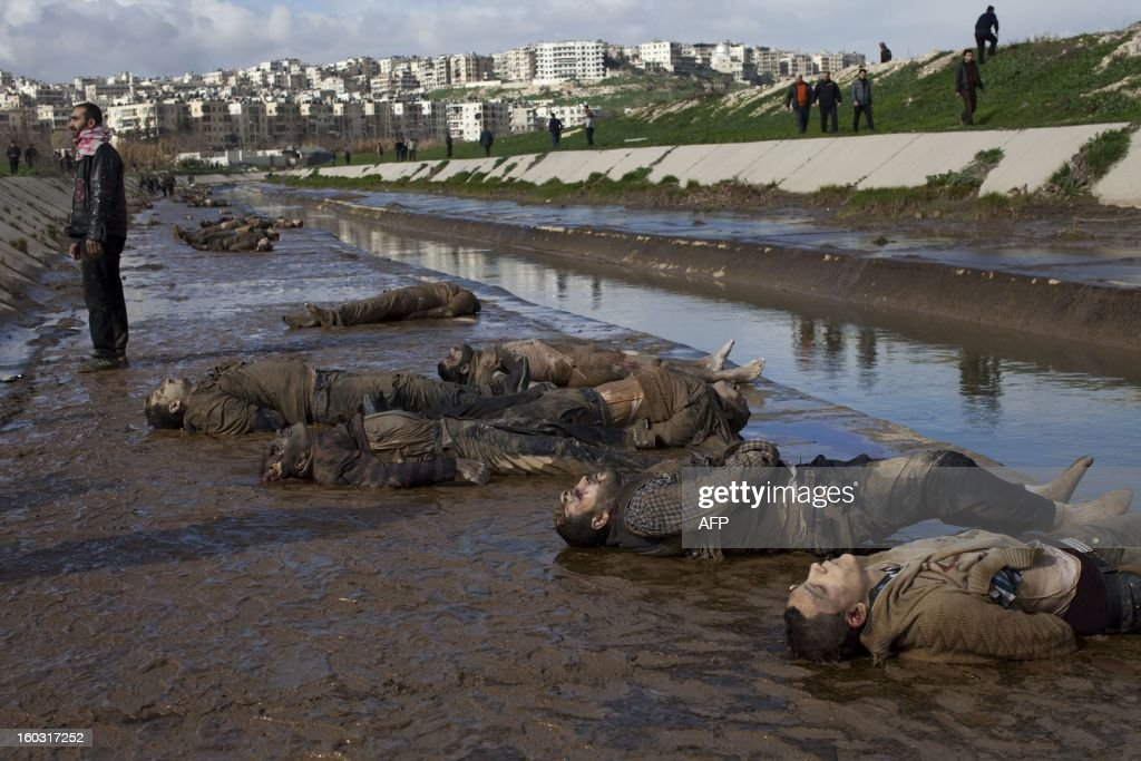 Syrian man stands next to the bodies of executed men on the side of a canal in the northern Syrian city of Aleppo on January 29, 2013. The bodies of at least 68 unidentified young men and boys, all executed with a single gunshot to the head or neck, were found in the Quweiq River, which separates the Bustan al-Qasr district from Ansari in the southwest of Aleppo, in a rebel-held area where a Free Syrian Army captain said many more were still being dragged from the water.
