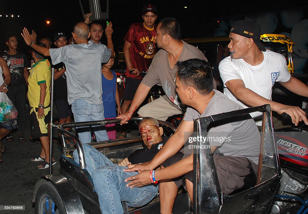 Graphic content / GRAPHIC In this picture taken on May 27, 2016, crime journalist Alex Balcoba, 56, is carried to a tricycle after he was shot by unidentified gunmen in Manila. A crime journalist has been shot dead in Manila, police and colleagues said on May 28, the latest addition to a lengthening list of unsolved murders of media workers in the Philippines. Balcoba, 56, was attacked in central Manila late Friday outside a watch repair shop owned by his family, the country's National Press Club said in a statement. CONTENT