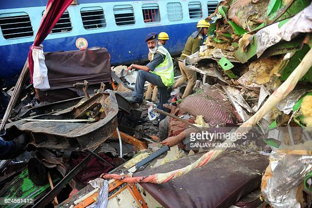 Graphic content / Indian rescue personnel stand near a body in the wreckage of a train that derailed near Pukhrayan in Kanpur district on November 20...