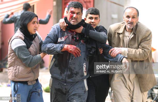 Graphic content / Iraqi civilians help a man who was injured by a mortar shell fired by Islamic State group jihadists on civilians in AlRisala...