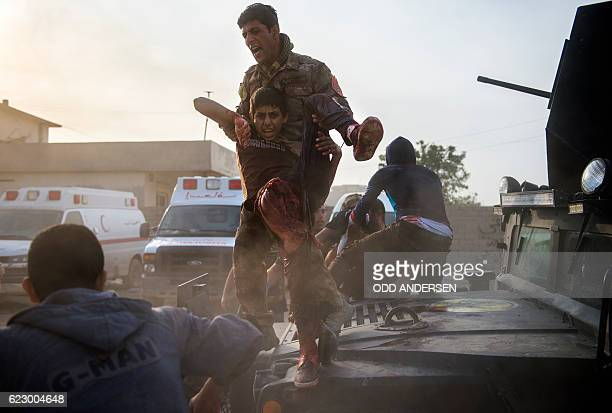 Graphic content / Iraqi soldiers and family rush 12yearold Mohammed and 15 year old Shafiq to an outdoor field clinic on their Humvee in the Samah...