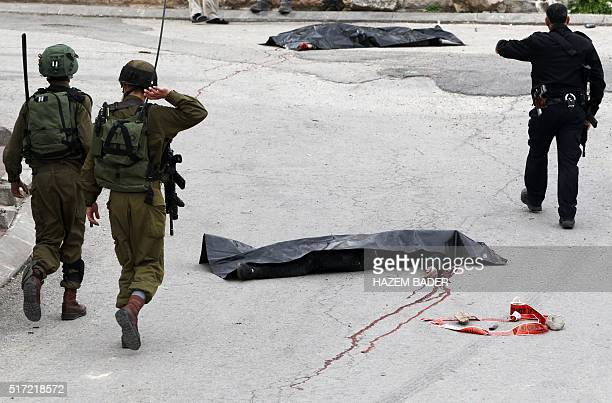 Graphic content / Israeli soldiers and police gather around the body of a Palestinian assailant who was allegedly shot in the head by an Israeli...