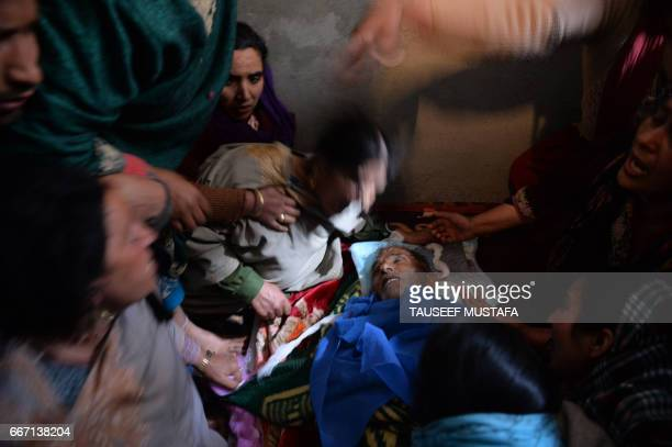 Graphic content / Kashmiri relatives mourn near the body of Ali Muhammad Dagga a private taxi driver who died when when he and the car he was driving...