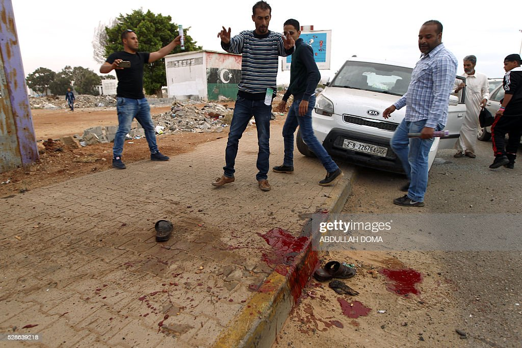 Graphic content / Libyans look at blood stains on the ground after shelling hit a demonstration in the eastern coastal city of Benghazi calling for military forces to re-capture the southern city of Sirte from the Islamic State (IS) group without foreign intervention on May 6, 2016. The head of Libya's unity government announced plans the previous month for a concerted campaign to drive the Islamic State group out of the North African country, but without foreign intervention. The unity government fears that separate operations in Sirte could spark clashes between the multitude of different fighting forces in Libya and play into the jihadists' hands. DOMA