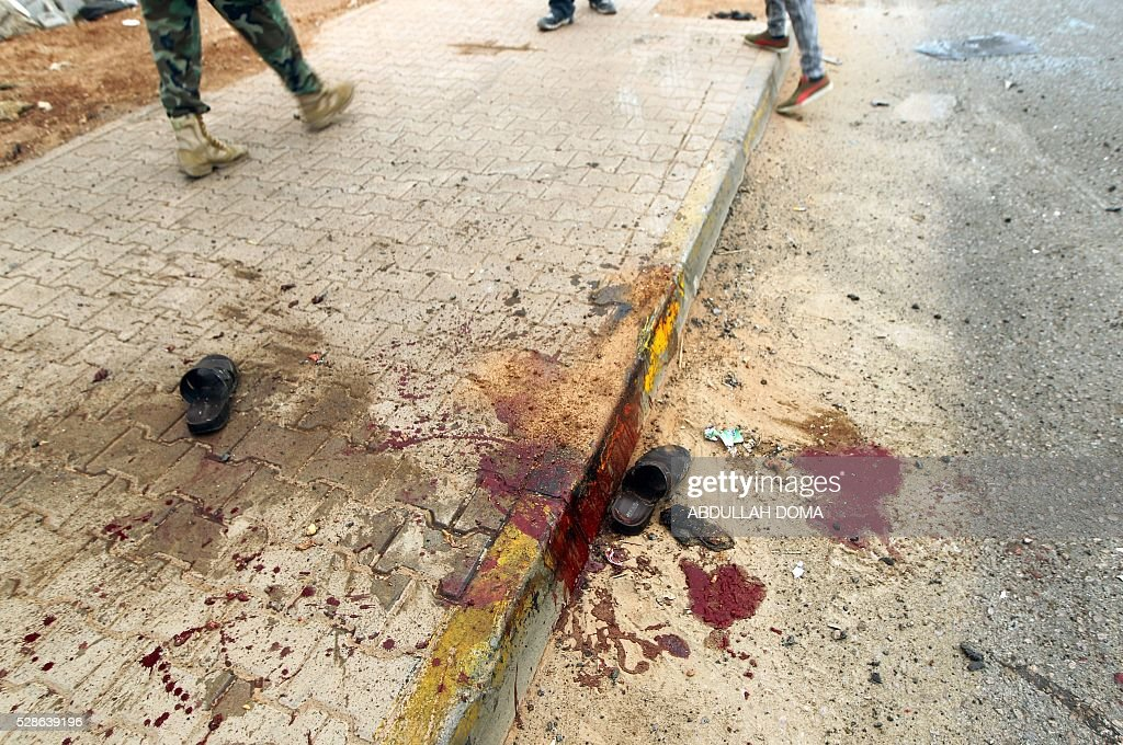 Graphic content / Libyans walks past blood stains on the ground after shelling hit a demonstration in the eastern coastal city of Benghazi calling for military forces to re-capture the southern city of Sirte from the Islamic State (IS) group without foreign intervention on May 6, 2016. The head of Libya's unity government announced plans the previous month for a concerted campaign to drive the Islamic State group out of the North African country, but without foreign intervention. The unity government fears that separate operations in Sirte could spark clashes between the multitude of different fighting forces in Libya and play into the jihadists' hands. DOMA