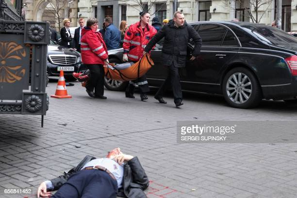 Graphic content / Medical workers carry the alleged gunman wounded after he shot dead former Russian MP Denis Voronenkov in central Kiev on March 23...