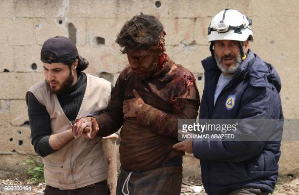Graphic content / Members of the Syrian civil defence volunteers also known as the White Helmets help a man after removing him from the rubble of his...