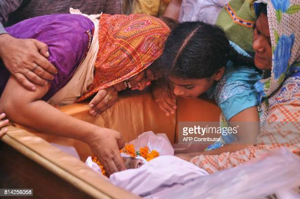 Graphic content / Neha Devi and Kajal wife and daughter of slain Indian soldier Lance Naik Ranjeet Singh mourn over his body at his home in Burn...