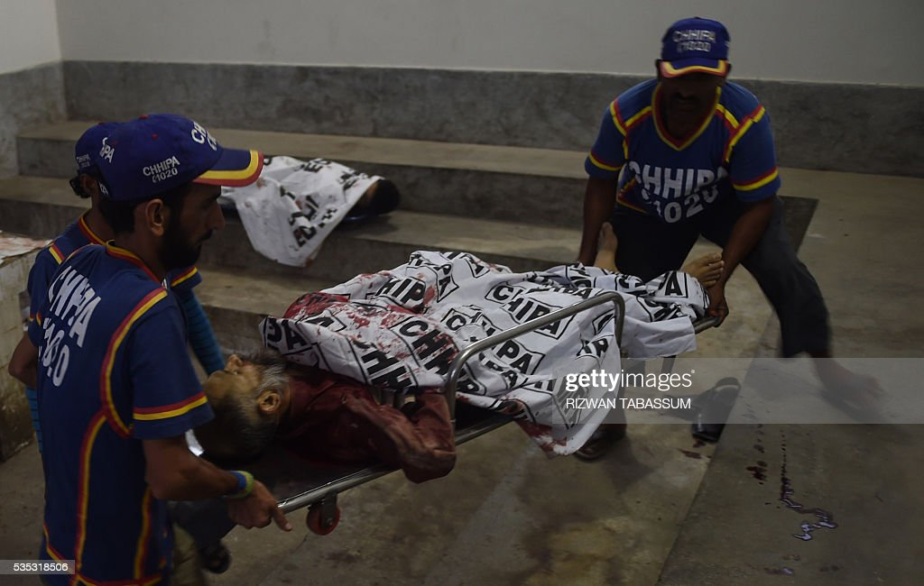 Graphic content / Pakistani rescuers shift the bodies of Al-Qaeda militants into a mortuary in Karachi on May 29, 2016. Pakistani police have killed three Al-Qaeda militants during a gunfight in the southwestern port city of Karachi after raiding their hideout, officials said. GRAPHIC