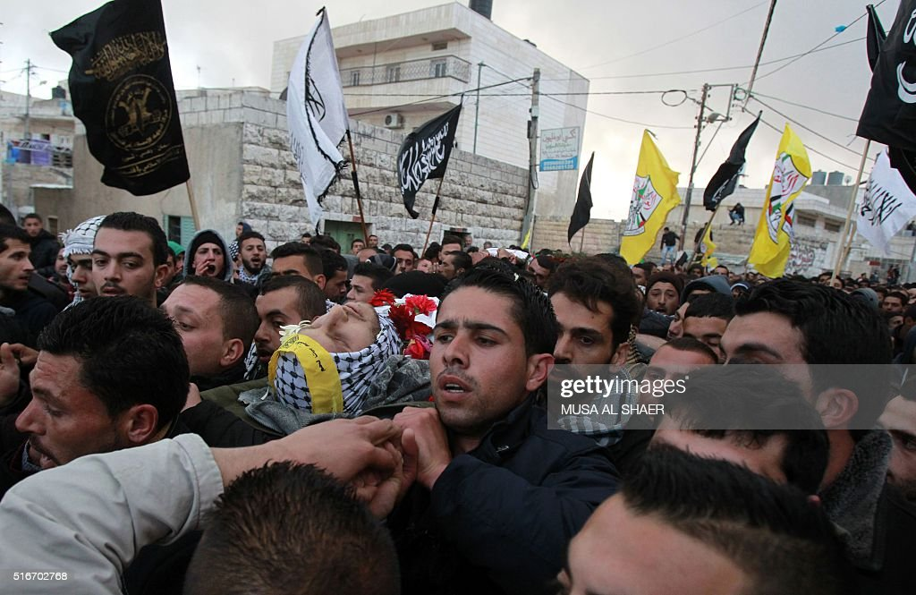Graphic content / Palestinian mourners carry the body of Ali Thawabteh during his joint funeral procession with his friend Ali Taqatqah who was...