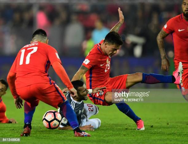 Graphic content / Paraguay's Antonio Barreiro and Chile's Charles Aranguiz fall during their 2018 World Cup qualifier football match in Santiago on...