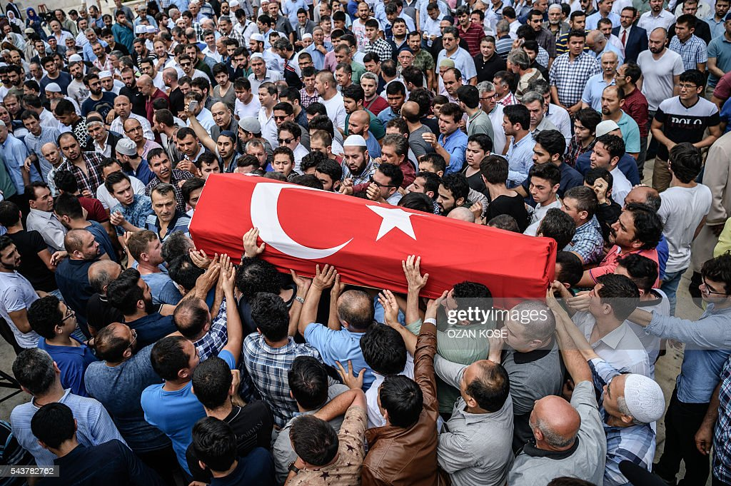 People carry a coffin covered with Turkish national flag of suicide attack victim Hamidullah Safar on June 30, 2016 in Istanbul during his funeral two days after a suicide bombing and gun attack targeted Istanbul's airport, killing at least 36 people. The death toll from the triple suicide bombing and gun attack that occurred on June 28, 2016 at Istanbul's Ataturk airport has risen to 43 including 19 foreigners. The government has pointed the finger of blame at the Islamic State group and Turkish police rounded up 13 suspected IS jihadists in raids at 16 different locations across Istanbul on June 30. KOSE