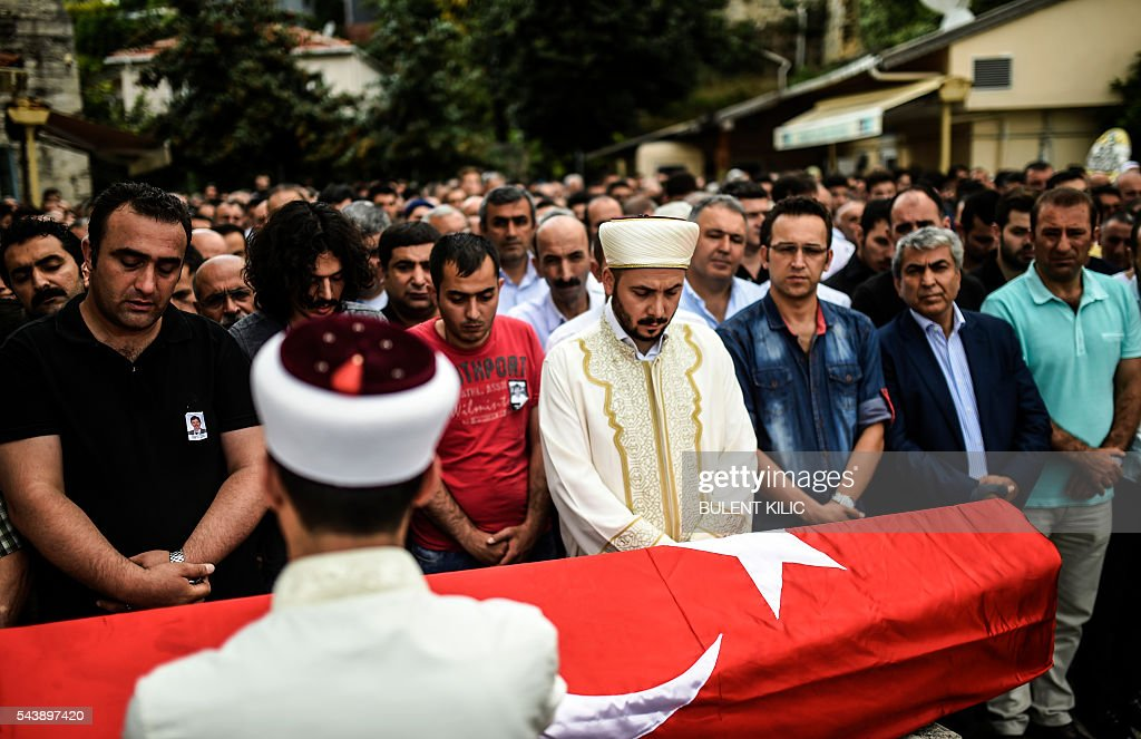 People gather in front of the coffin for the funeral of Turkish teacher Huseyin Tunc in Istanbul on June 30, 2016 two days after the triple suicide bombing and gun attack occurred at Istanbul's Ataturk airport. The death toll from the triple suicide bombing and gun attack that occurred on June 28, 2016 at Istanbul's Ataturk airport has risen to 43 including 19 foreigners. The government has pointed the finger of blame at the Islamic State group and Turkish police rounded up 13 suspected IS jihadists in raids at 16 different locations across Istanbul on June 30. / AFP / BULENT