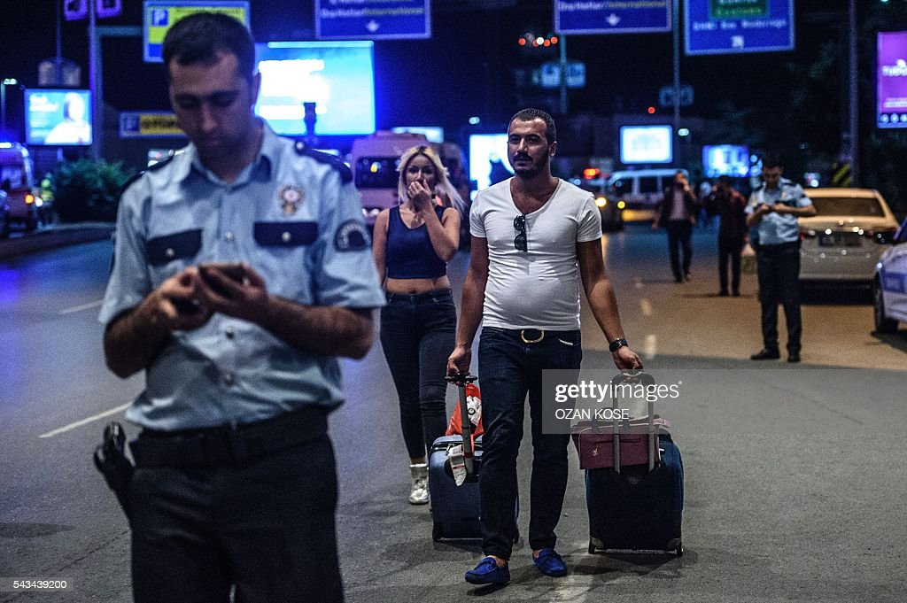 Graphic content / People leave the airport after two explosions followed by gunfire hit the Turkey's biggest airport of Ataturk in Istanbul, on June 28, 2016. At least 10 people were killed on June 28, 2016 evening in a suicide attack at the international terminal of Istanbul's Ataturk airport, Turkish Justice Minister Bekir Bozdag said. Turkey has been hit by a string of deadly attacks in the past year, blamed on both Kurdish rebels and the Islamic State jihadist group. / AFP / OZAN