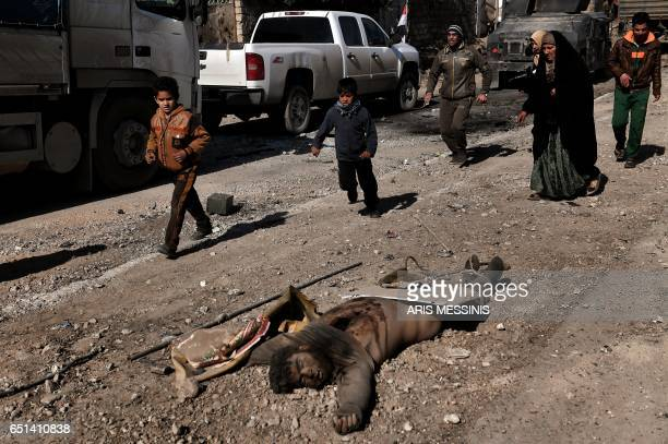 Graphic content / People pass by the body of a reported jihadist in west Mosul on March 10 2017 as Iraqi forces advance in the city in the ongoing...