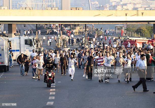 Graphic content / People run away from tanks after taking over military position on the Bosphorus bridge in Istanbul on July 16 following an attempt...