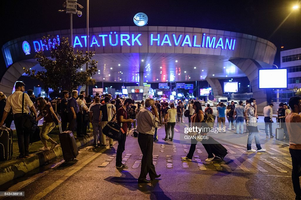 Graphic content / People stand outside the entrance as they leave the airport after two explosions followed by gunfire hit the Turkey's biggest airport of Ataturk in Istanbul, on June 28, 2016. At least 10 people were killed on June 28, 2016 evening in a suicide attack at the international terminal of Istanbul's Ataturk airport, Turkish Justice Minister Bekir Bozdag said. Turkey has been hit by a string of deadly attacks in the past year, blamed on both Kurdish rebels and the Islamic State jihadist group. / AFP / OZAN