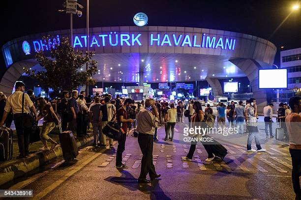 Graphic content / People stand outside the entrance as they leave the airport after two explosions followed by gunfire hit the Turkey's biggest...