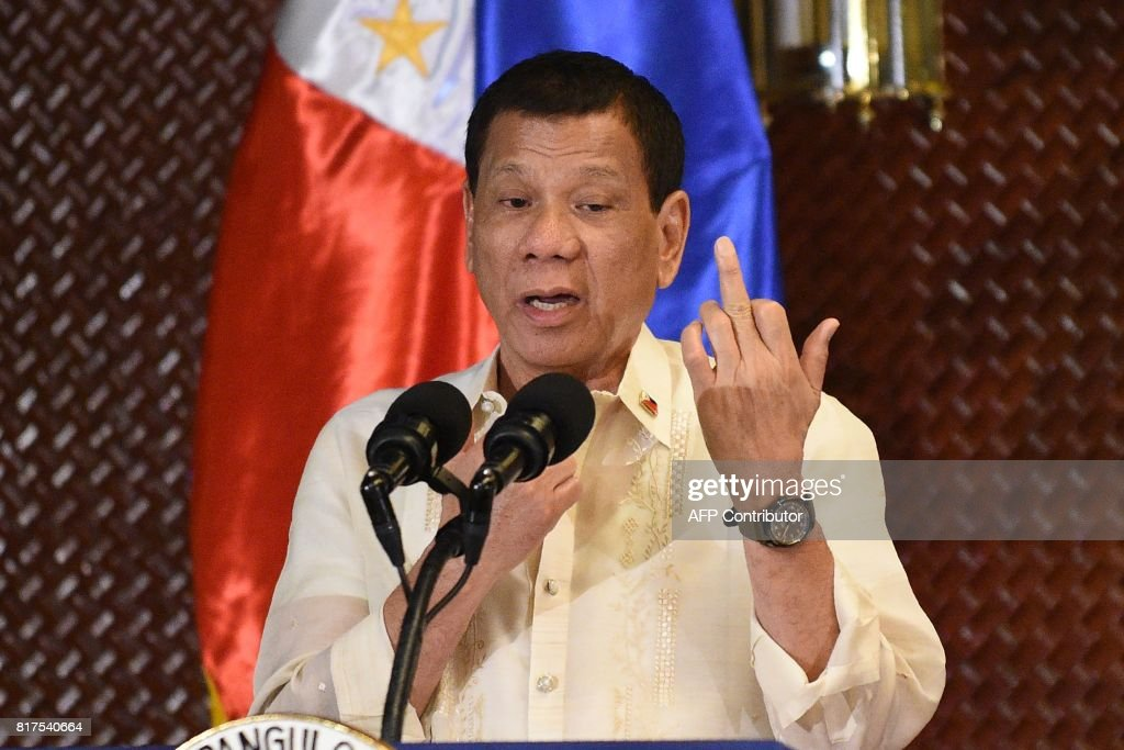 Graphic content / Philippine President Rodrigo Duterte gestures the middle finger in an address to military personnel to not give up their weapons so easily while facing the enemy, during a turn-over of some 3,000 .45 caliber handguns to the military at Malacanang Palace in Manila on July 18, 2017. President Duterte announced plans July 18 to extend martial law in the southern Philippines to defeat Islamist militants who have seized a major city, as critics warned the country could be edging towards a dictatorship. /