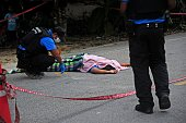 Graphic content / Police officers inspect the body of a woman after she was killed by suspected separatist militants in the Takbai district of...