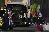 Graphic content / Police officers stand near a truck with its windscreen riddled with bullets that ploughed into a crowd leaving a fireworks display...