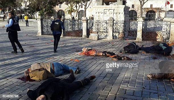 Graphic content / Police stand beside victims at the site of a blast in Istanbul's Sultanahmet district the city's main tourist hub on January 12...