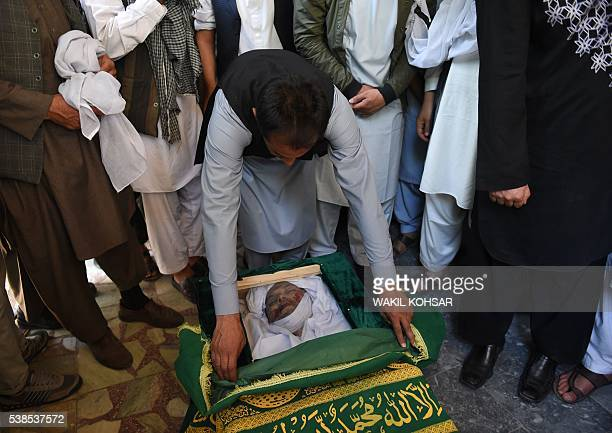 Graphic content / Relatives and friends gather around the coffin of Afghan reporter Zabihullah Tamanna before his funeral prayers at a mosque in...