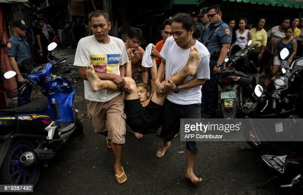 Graphic content / Residents carry a body of an alleged drug dealer killed during a large scale antidrug raid by the police at a slum community in...