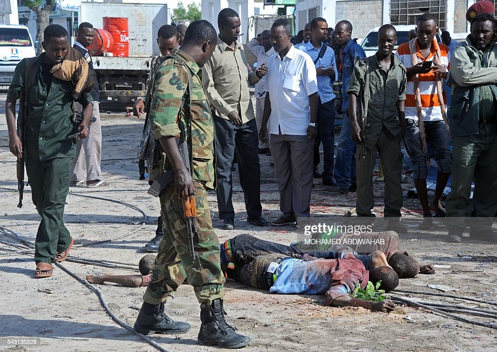 Graphic content / Somali soldiers and people stand and look at the bodies of three suspected fighters of the radical Islamist al-Shabab group lying in the road outside The Nasahablood Hotel in Mogadishu on June 26, 2016, a day after an attack in which at least 11 people were killed. At least 11 people were killed on June 25, 2016 in an attack on a hotel in the Somali capital Mogadishu that was swiftly claimed by Al-Qaeda-affiliated Shabaab militants. The assault, the latest in a series by the Islamist group targeting hotels and restaurants, began when a suicide bomber detonated a car laden with explosives outside the building. ABDIWAHAB