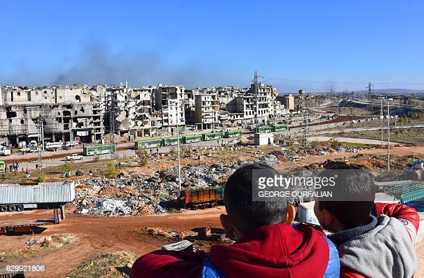 Graphic content / Syrian children watch on as buses depart during an evacuation operation of rebel fighters and their families from rebelheld...