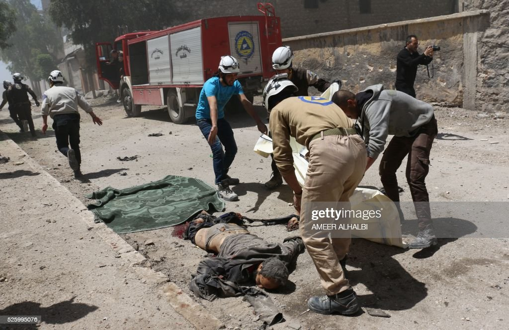 Graphic content / Syrian civil defence volunteers remove a body following a reported air strike on the rebel-held eastern neighbourhood of Bab al-Nayrab in Syria's second city Aleppo, on April 29, 2016. Fresh bombardment shook Syria's second city Aleppo, severely damaging a local clinic as outrage grows over an earlier air strike that destroyed a hospital. The northern city has been battered by a week of air strikes, rocket fire, and shelling, leaving more than 200 civilians dead across the metropolis. The renewed violence has all but collapsed a fragile ceasefire deal that had brought an unprecedented lull in fighting since February 27. / AFP / AMEER