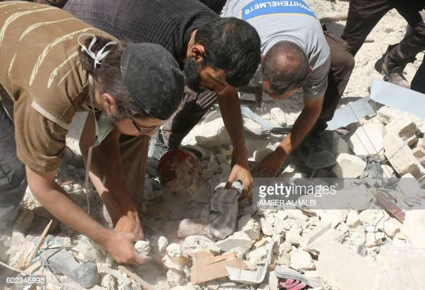 Graphic content / Syrian men remove a victim from under the rubble of destroyed buildings following a reported air strike on the rebelheld Salihin...