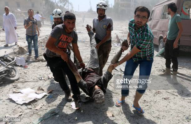 Graphic content / Syrian rescue workers and civilians evacuate a man in the Maadi district of eastern Aleppo after regime aircrafts reportedly...