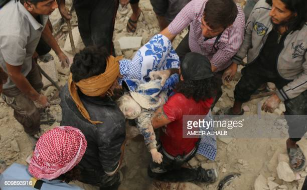 Graphic content / Syrians carry the body of child after pulling it out from under the rubble of a building following bombardment on the alMarja...